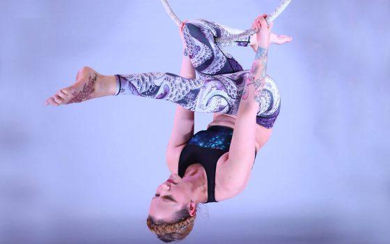 Girl hanging upside down on aerial hoop