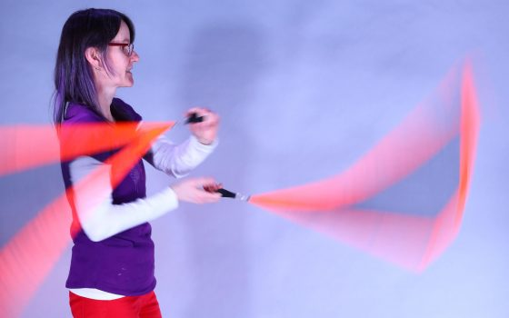 Woman twirling brightly coloured material